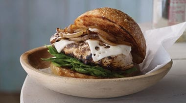 chicken breast sandwich with swiss cheese, spinach and grilled onions