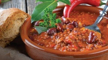 bowl of chili with garnish and crusty bread