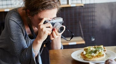 woman taking photo of food