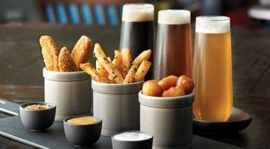 fried appetizers with glasses of beer