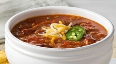chili in a white bowl topped with cheese and jalapeno