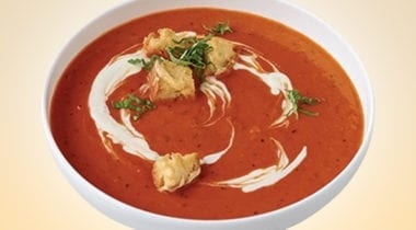 red pepper soup in a bowl with garnish