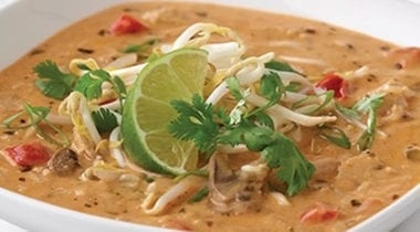 creamy thai soup topped with lime and garnish