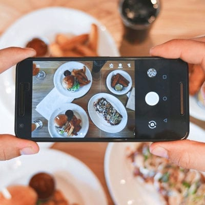 person holding smart phone taking photo of food