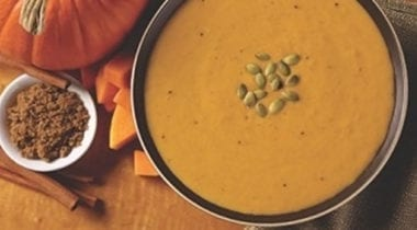pumpkin bisque soup topped with toasted pumpkin seeds