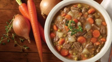 beef stew in a bowl with carrots and onion