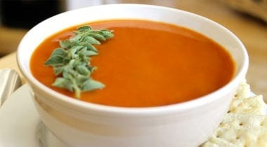 tomato soup in a white bowl with garnish