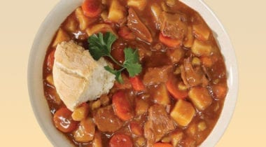beef stew in a bowl with bread and garnish