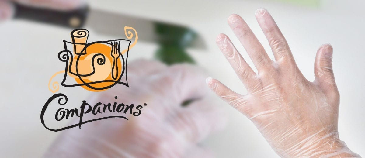 hand wearing clear gloves with companions logo