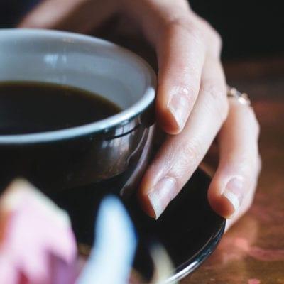 hands holding mug with black coffee
