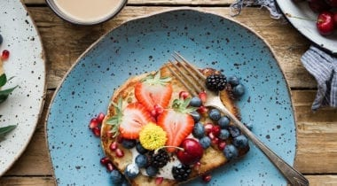 french toast and berries on colorful speckled plates
