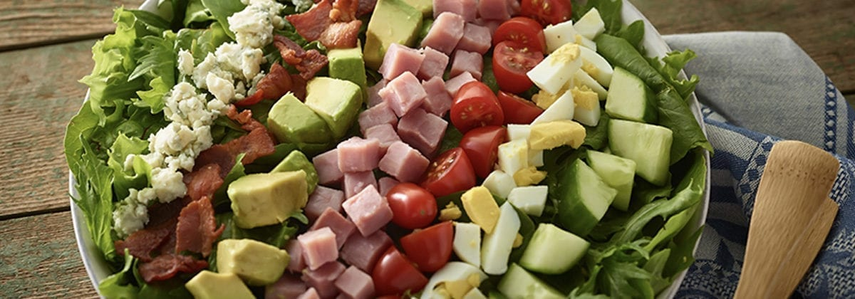 salad with diced cucumbers, egg, tomato, ham, avocado, bacon and bleu cheese