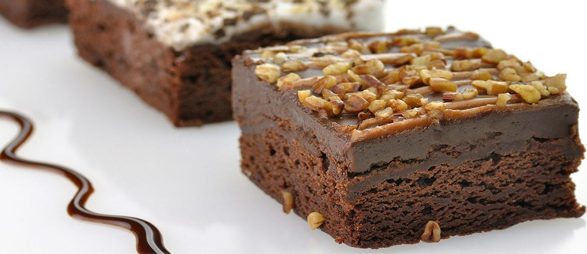 brownies with chocolate fudge topping and crushed walnut topping