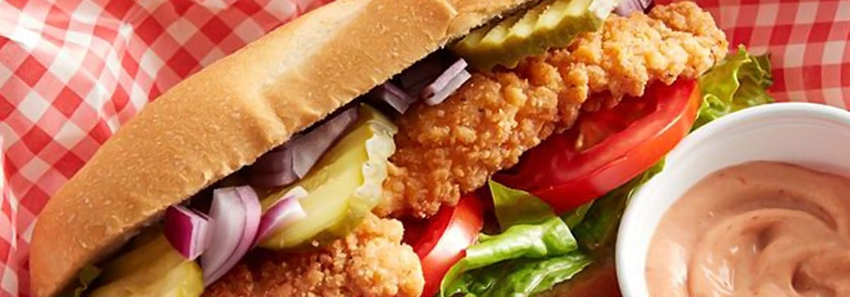 chicken sandwich with tomato, onions and pickles