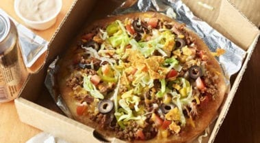 taco pizza with hormel beef crumble, lettuce, tortilla chips, tomatoes and black olives