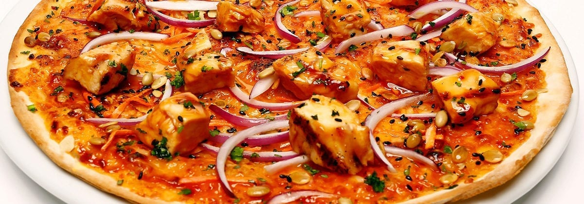 thai chicken with red onions on pizza