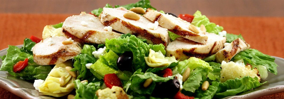 sliced grilled chicken on mediterranean salad