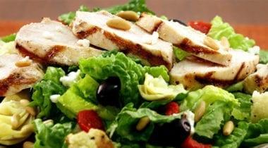 sliced grilled chicken on mediterranean salad