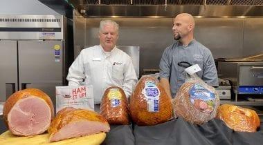 two men behind ham display