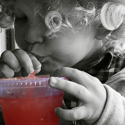 child sipping drink straw clear cup