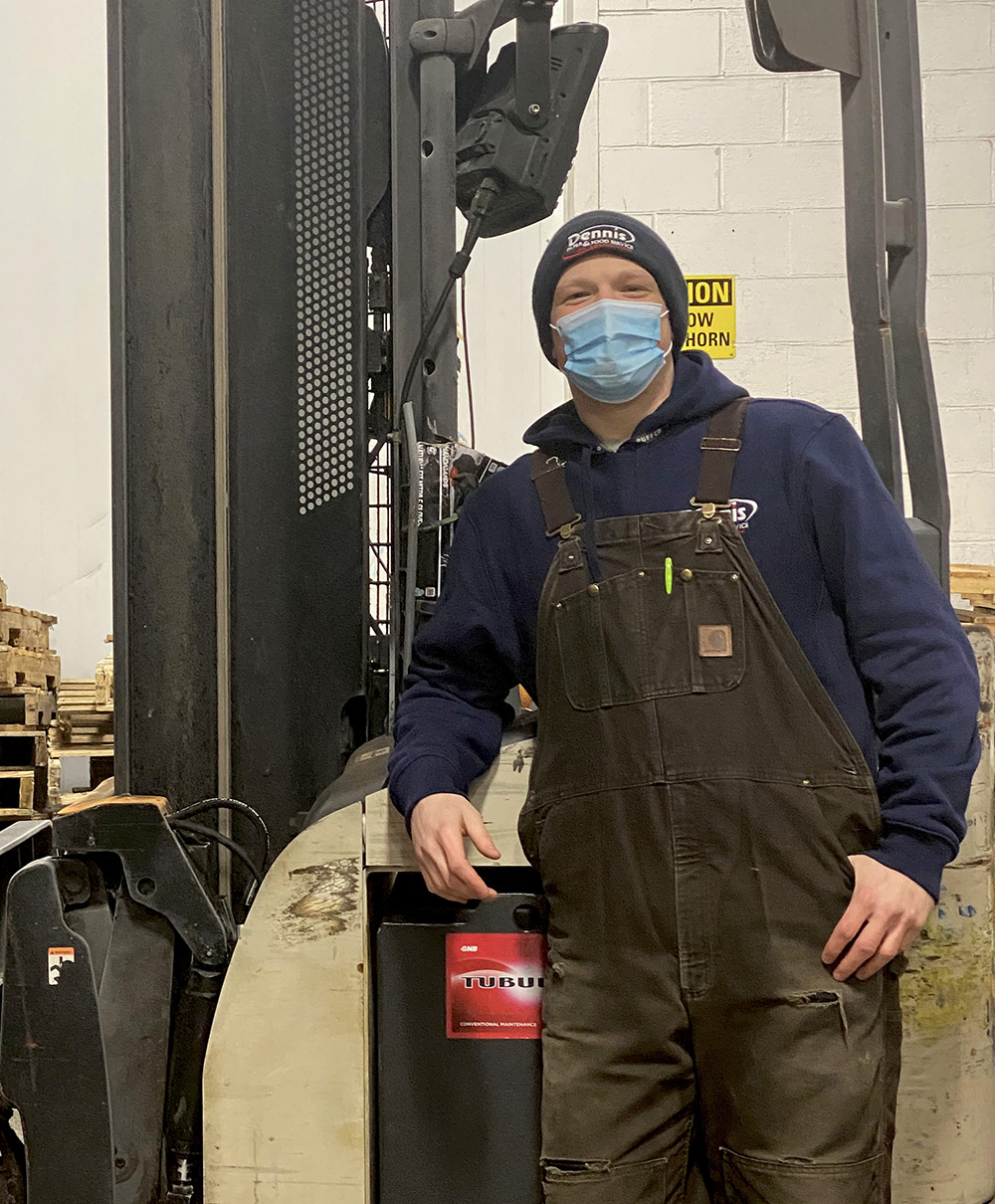 man standing by forklift with mask