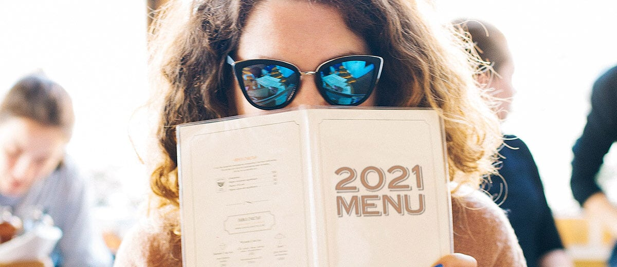 woman with sunglasses holding 2021 menu in front of face