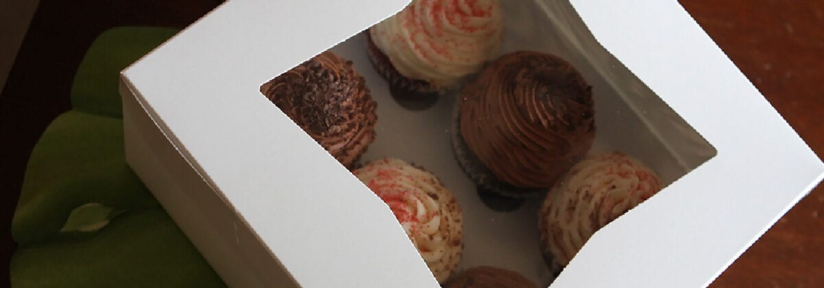white bakery box holding cupcakes