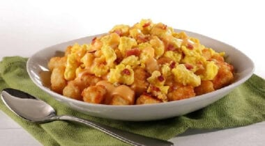 scrambled eggs with cheese and bacon on top of tater tots
