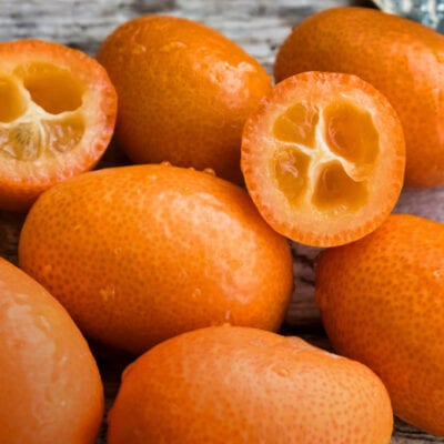 kumquats with kife on wood