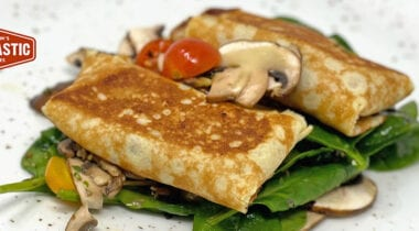 stuffed crepes on spinach with mushrooms