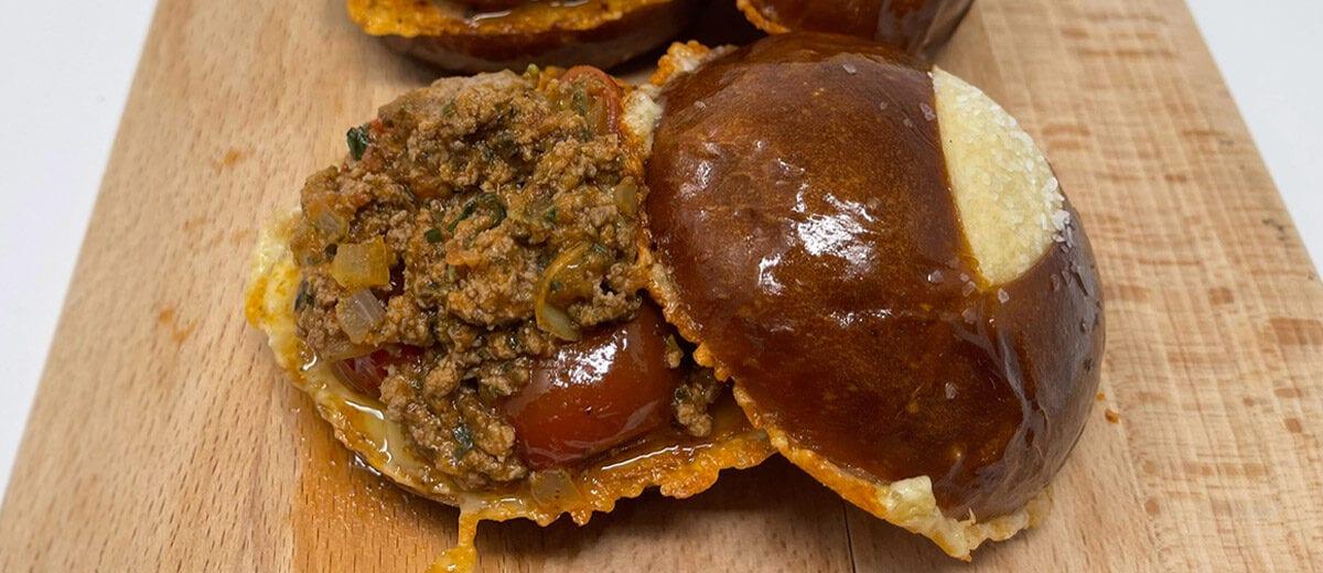sloppy joe sanwiches on pretzel buns, on cutting board
