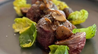beef medalions with Brussels sprout leaves and mushrooms