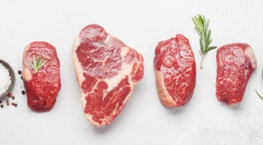 a variety of different steak cuts on white tabletop background next to sea salt and peppercorns as well as herbs