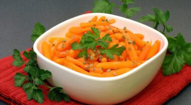 seasoned slim baby carrots in a white bowl placed on a grey countertop