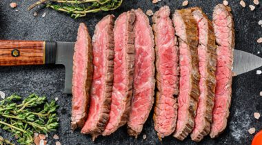 sliced flat iron steak on top of rustic knife on kitchen counter