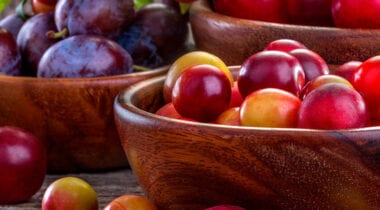 plums and stone fruits in wooden bowls